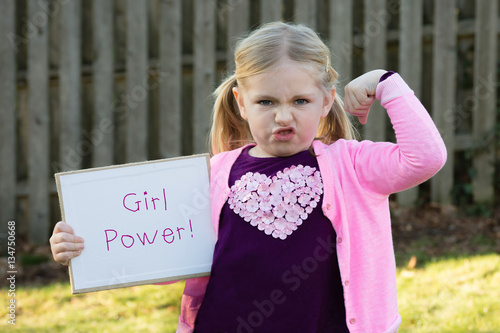 Photo  adorable school age girl wearing pink and holding sign saying girl power for wom