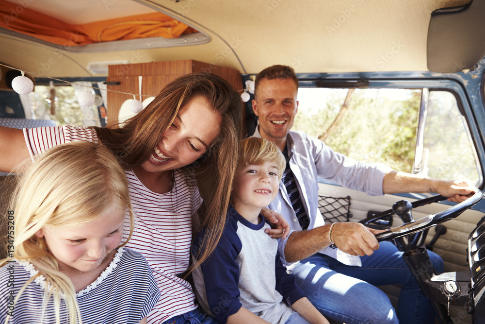 Fototapety, obrazy: Family sitting at the front of their camper van, dad driving