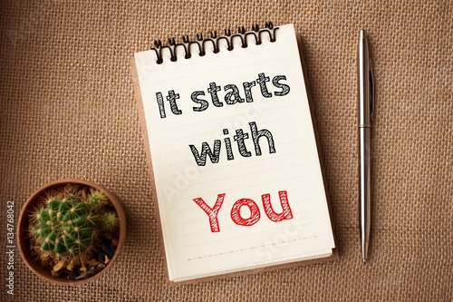 Fotografía  It starts with you, Text message on brown Notebook / business concept