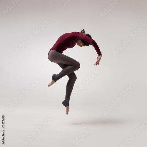 Tableau sur Toile young beautiful woman dancer with long brown hair wearing maroon swimsuit jumpin