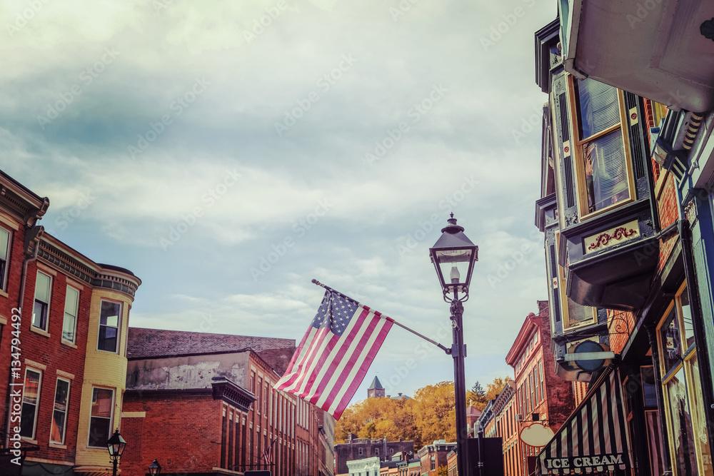 Fototapety, obrazy: Shops along main street, Galena, Illinois, focus on flag, toned