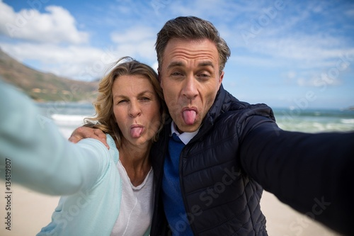 Fototapeta Mature couple sticking out tongue while taking selfie obraz na płótnie