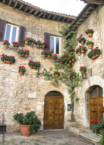 Fototapety, obrazy: Medieval corner with flower and pots in a small town in Italy.