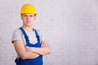 portrait of young handsome man in blue builder uniform over whit