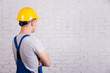 back view of man in blue builder uniform looking at white wall