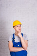builder in uniform and hard hat posing over white wall