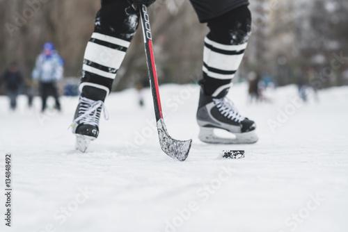 Plakat hokeista biegnie z krążkiem na lodzie