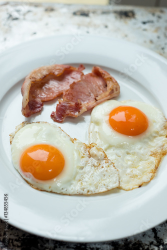 Foto op Plexiglas Gebakken Eieren Cooked Bacon and Eggs in White Plate