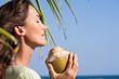 femme avec une noix de coco sous un paimier