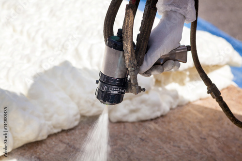 Obraz Technician spraying foam insulation using Plural Component Spray Gun - fototapety do salonu