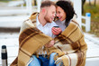 Young couple embracing and covered with a warm blanket sitting o