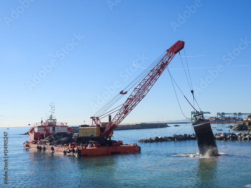 Fényképezés  Grab Dredge with Clamshell Bucket unloading gravel to replenish