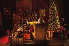 Santa Sits At His Desk, Surrounded By Festive Christmas Decor And Presents