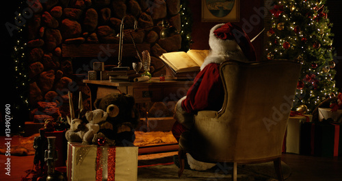 Canvas Print Santa Claus works at his desk, surrounded by Christmas decorations