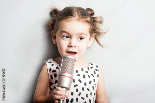 Happy Cute little girl singing a song on microphone  Grey