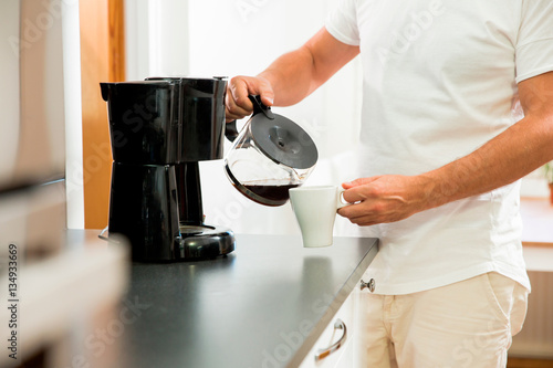 Man in the kitchen pouring a mug of hot filtered coffee from a glass pot Fototapet