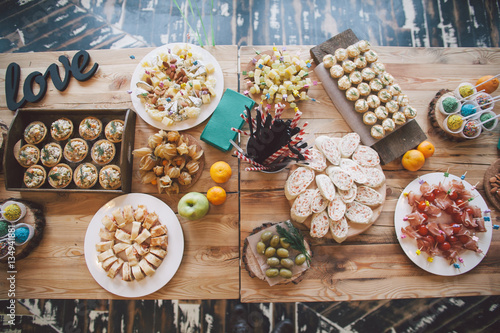 Wooden table with different type of snacks preparing for party.