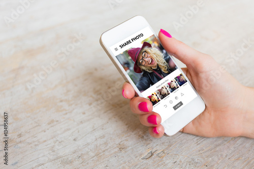 Obraz Woman using photo sharing app on phone - fototapety do salonu