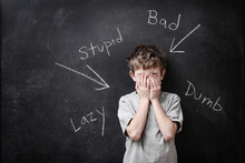 Abusive Words Written On A Blackboard With A Child Covering His
