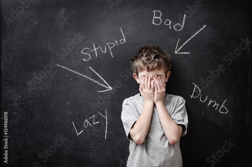 Abusive words written on a blackboard with a child covering his Wallpaper Mural