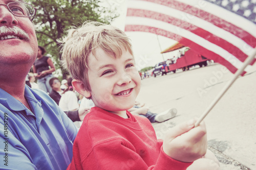 Photo Boy and his father watching a parade