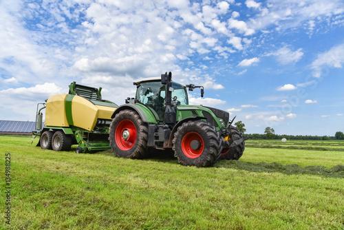 Ernte - Traktor mit Rundballenpresse im Einsatz für Grasssilage Poster Mural XXL