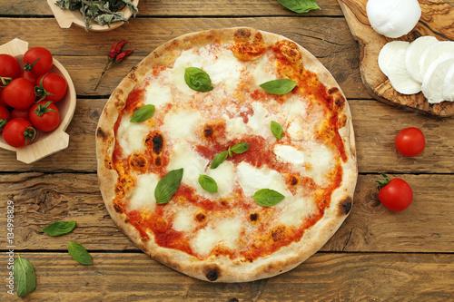 Foto op Canvas Madeliefjes pizza margherita su sfondo rustico
