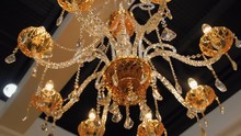 Beautiful Golden Color Crystal Chandelier Illuminates All Around Warm Amber Light. Shot In Motion