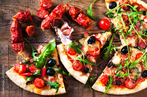 Hot pizza slice with meat and cheese on  wooden table close up.. © nataliazakharova