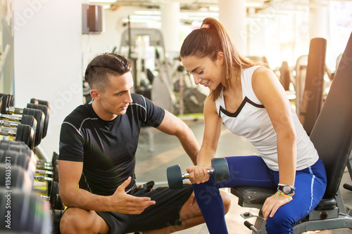 Personal trainer working with his client in gym. Young male personal trainer talking with young fitness woman while she lifting weights.