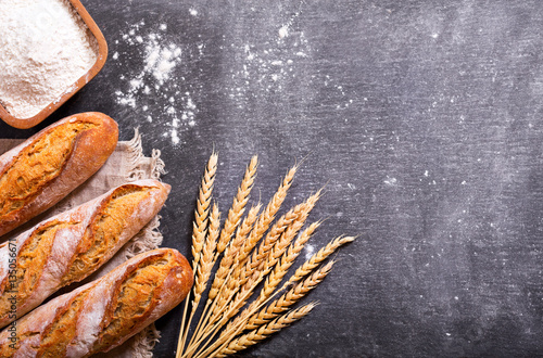 Foto op Canvas Brood bread with wheat ears and bowl of flour