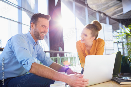 Fototapety, obrazy: Young smiling couple sharing a laptop