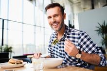 Smiling Man Eating In Cafe