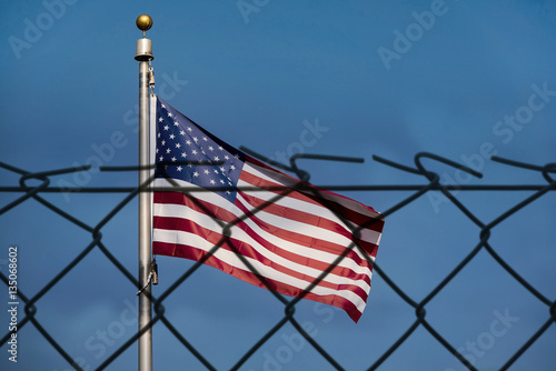 Photo  American flag and defocused fence, the United States confrontation and refugees