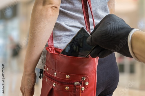 Fotografía Pickpocket thief is stealing smartphone from red handbag.