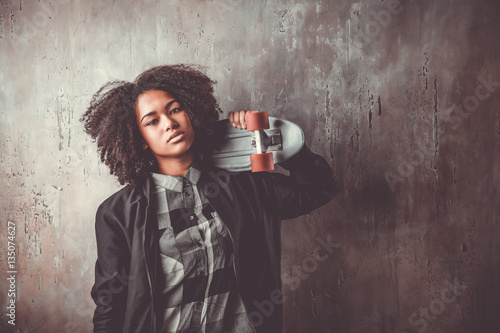 Vászonkép African teenager girl with skateboard in front of a concrete wall