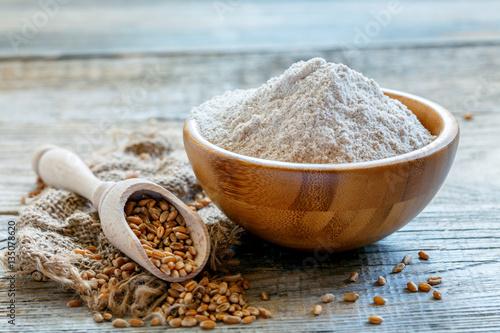 Fototapeta Wheat wholemeal flour in a wooden bowl. obraz