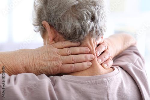 Fotografía  Elderly woman suffering from neck pain, closeup