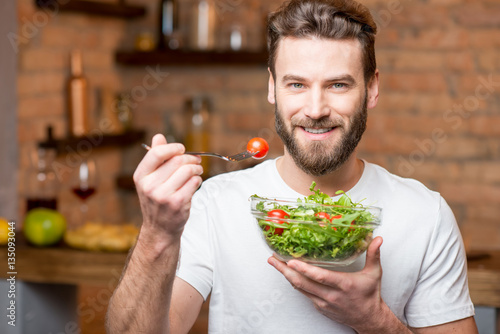 Fotografie, Obraz  Handsome bearded man in white t-shirt eating salad with tomatoes in the kitchen