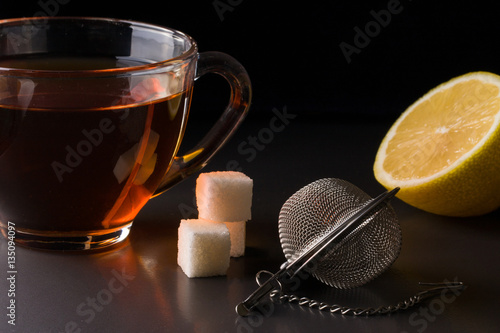 Fényképezés cup of tea with a strainer and  lemon on  dark background
