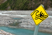 Flash Flood Warning Sign On A Rocky Riverbed In New Zealand