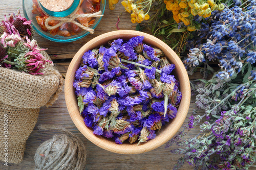 Photo  Medicinal herbs, mortar and bag of dry healthy flowers on wooden board