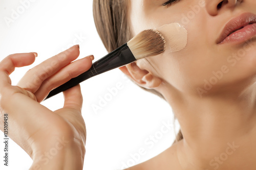 Fotografía  A young woman applied liquid foundation on her face with a brush