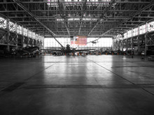 The American Flag Stands Out In The Background Of This Black And White Photo Of An Airplane Hangar.