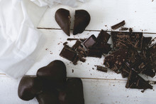 Broken Dark Chocolate And Chocolate Hearts With Tissue On The White Wooden Table. Selective Focus And Small Depth Of Field.