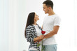 Happy couple with red rose at home