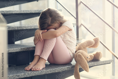 Photo Sad little girl sitting on stairs