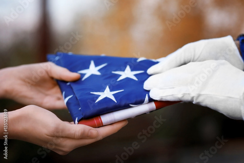 Photo  Hands holding folded American flag on blurred background
