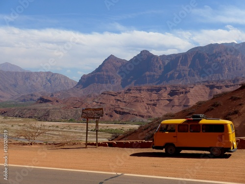 Photo  Yellow Kombi parked in front of red dry valley on the way to Cafayate in Nth Argentina