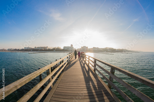 Canvas Prints Cappuccino Pier of kuehlungsborn with view of the skyline of the city in the sunset at the baltic sea